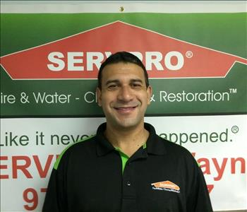 Male employee smiling in front of SERVPRO logo